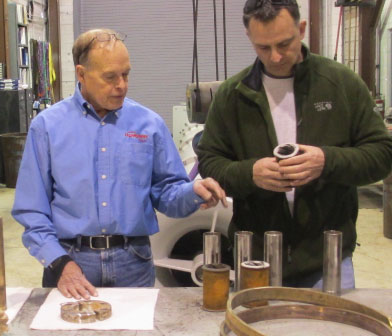 Siewert reliability engineer reviewing worn pump components with Cornell University Plant Engineer