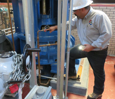 Siewert reliability engineer inspecting seal flush piping plan at City of Buffalo water plant