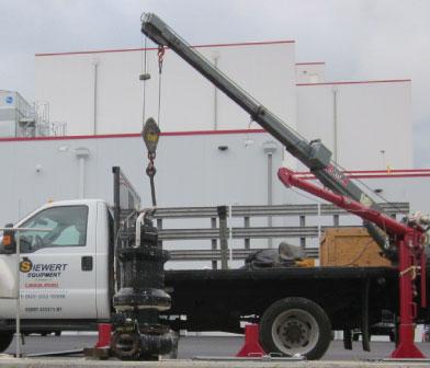 Siewert Equipment crane truck loading a submersible pump.