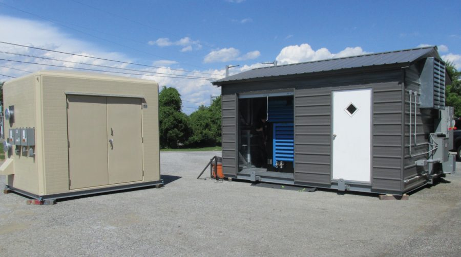 Two custom process equipment packages in fabricated building enclosures outside.