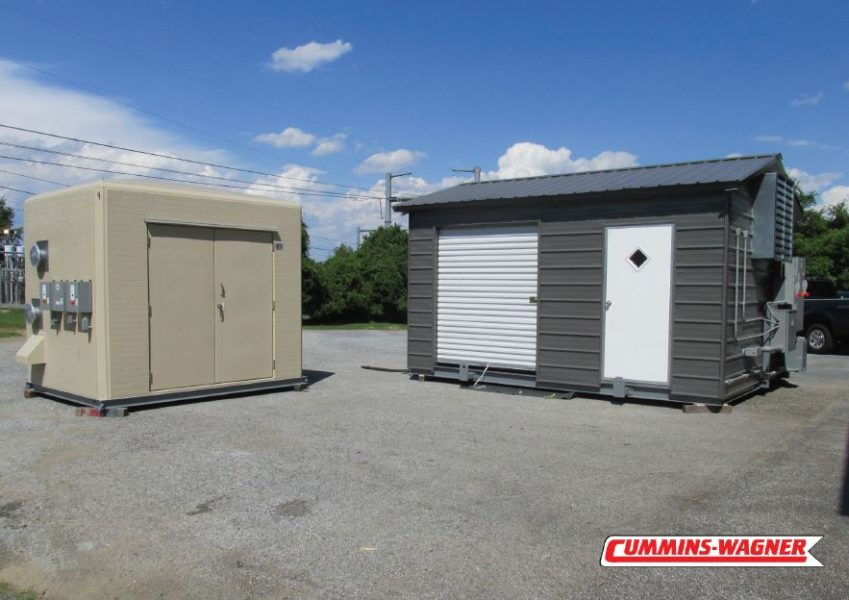 Weatherproof custom fiberglass enclosure next to a painted metal building with exterior process connections.